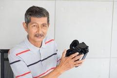 Gamal man i vrverklighetexponeringsglas av virtuell verklighet royaltyfri foto