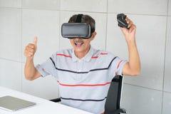 Gamal man i vrverklighetexponeringsglas av virtuell verklighet med att spela leken royaltyfria foton