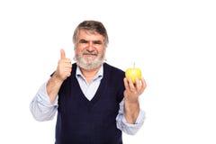 Gamal man med äpplet i händer Arkivbild