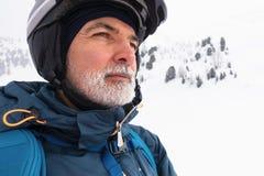 Gamal man med det vita skägget på det snöig berget royaltyfria bilder