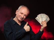 Gamal man med dollarräkningar Arkivbild