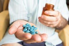 Gamal man med en hög av blåa preventivpillerar i hans hand Royaltyfri Bild
