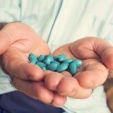 Gamal man med en hög av blåa preventivpillerar i hans hand Royaltyfri Foto
