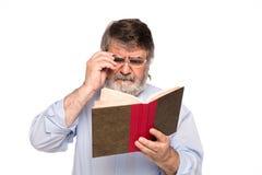 Gamal man med exponeringsglas som läser en bok royaltyfri fotografi
