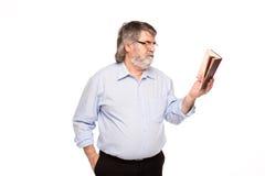 Gamal man med exponeringsglas som läser en bok arkivfoto