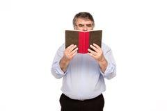 Gamal man med exponeringsglas som läser en bok royaltyfria bilder