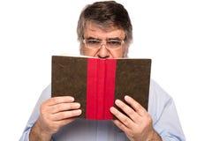 Gamal man med exponeringsglas som läser en bok Royaltyfri Foto