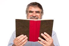 Gamal man med exponeringsglas som läser en bok arkivbilder