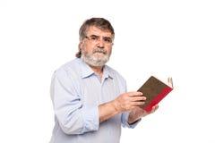 Gamal man med exponeringsglas som läser en bok arkivfoton