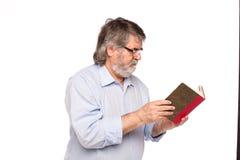 Gamal man med exponeringsglas som läser en bok arkivbild