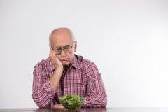 Gamal man med grön sallad fotografering för bildbyråer