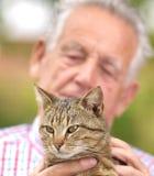 Gamal man med katten Arkivbild
