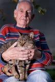 Gamal man med katten Arkivfoto