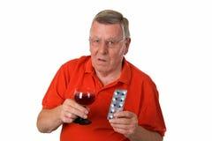 Gamal man med rött vin och pills Arkivbild