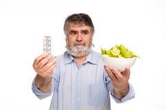 Gamal man med sallad och preventivpillerar royaltyfria foton