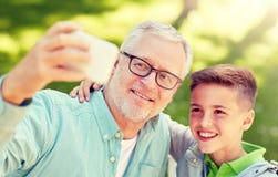 Gamal man och pojke som tar selfie vid smartphonen royaltyfria bilder
