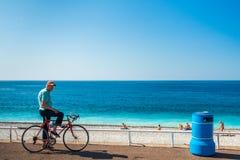 Gamal man på cykeln på beachfront Arkivfoton