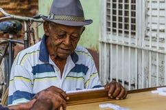 Gamal man på gatan av Trinidad som spelar dominobricka Royaltyfria Bilder