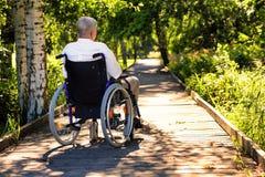Gamal man på rullstolen på banan i parkera Royaltyfria Foton