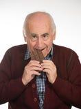 Gamal man som äter choklad royaltyfri bild