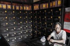 Gamal man som äter jordnötter i ett gammalt apotek, Hoi An, Quảng Nam Province, Vietnam royaltyfria foton
