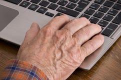 Gamal man som använder bärbara datorn Arkivfoto