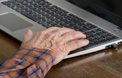 Gamal man som använder bärbara datorn Arkivbild