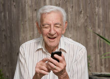 Gamal man som använder den smart telefonen arkivfoto