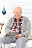 Gamal man som använder minnestavladatoren Arkivfoton