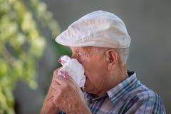 Gamal man som blåser näsan i servett arkivfoto