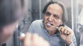 Gamal man som framme borstar tänder av spegeln royaltyfri fotografi