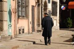 Gamal man som går i gammal stad Royaltyfri Bild
