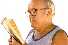 Gamal man som läser en bok Fotografering för Bildbyråer