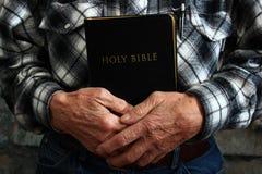 Gamal man som rymmer en bibel Arkivfoto