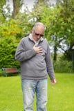Gamal man som rymmer hans bröstkorg Arkivbilder