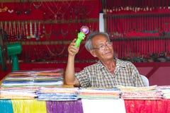 Gamal man som säljer souvenir på marknadsföra i Thailand Arkivbilder