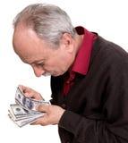 Gamal man som ser dollarräkningar Arkivfoton