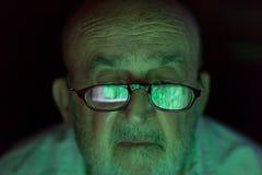 Gamal man som ser en hackad datorskärm arkivbild