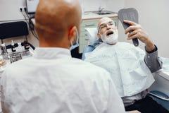 Gamal man som sitter i tandläkarens kontor royaltyfri fotografi