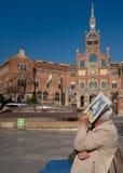 Gamal man som sitter på bänk nära den härliga byggnaden av Sant Pau Hospital i Barcelona, Catalonia, Spanien arkivbilder