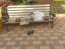 Gamal man som sover på bänk Arkivbilder