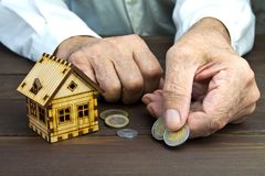 Gamal manhänder och ett modellhem med mynten på tabellen Begreppet av intecknar och banklån armod Uthyrnings- egenskap Ris Arkivbilder