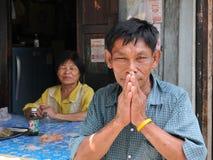 Gamal manhonnörer med en traditionell thailändsk hälsning arkivfoto