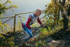 Gamal manidrottsman nenspring på bergslinga med nordiska gå poler Arkivfoto