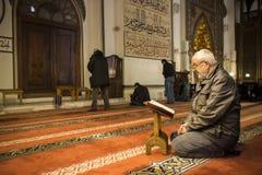 Gamal manläsningQuran i moské royaltyfria foton