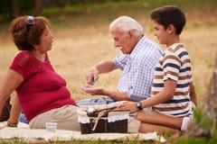 Gamal manmorfar med familjen som tar medicinpreventivpilleren för hjärta Arkivbilder