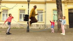 Gamal manrep som hoppar over med tre flickor lager videofilmer