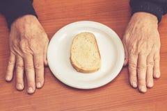Gamal mans händer på tabellen med en skiva av bröd i mitt arkivfoto