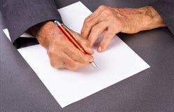Gamal mans händer som skriver med en penna royaltyfria foton