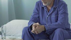 Gamal mansammanträde i pajama på säng med preventivpillerar i bunke på natttabellen som är deprimerad arkivfilmer